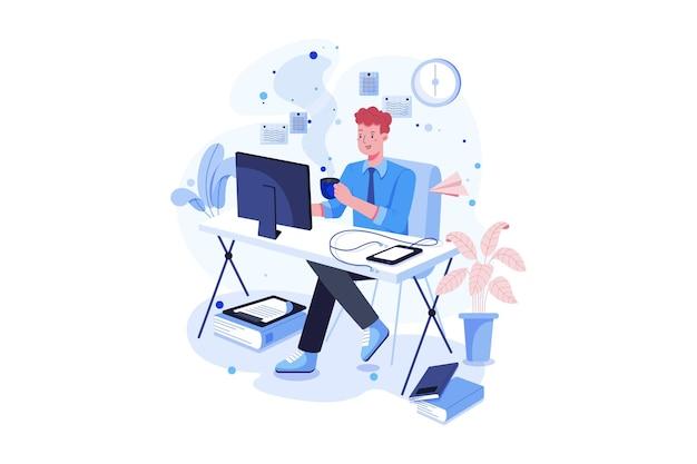 Молодой человек сидит за столом с компьютером и пьет кофе