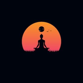 日没の背景を持つ若い男の瞑想