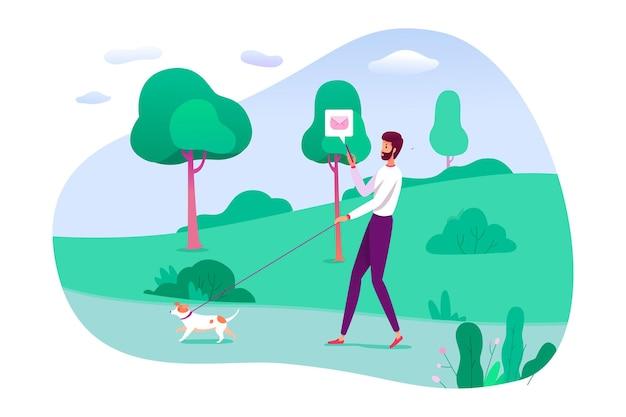 도시 공원에서 야외 가죽 끈에 개를 산책 하는 동안 네트워킹 하는 젊은 남자. 소셜 미디어 네트워크에서 채팅, 도보로 이메일 보내기