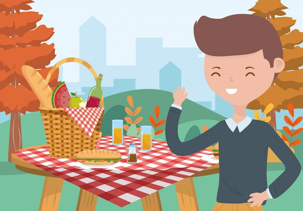 Young man picnic basket food table tablecloth nature cityscape