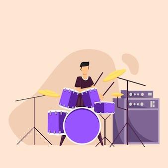 若い男がドラムセットで演奏