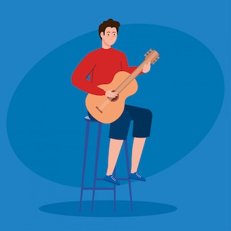 Молодой человек играет на гитаре, сидя на стуле
