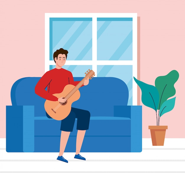 Young man playing guitar sitting a couch in living room