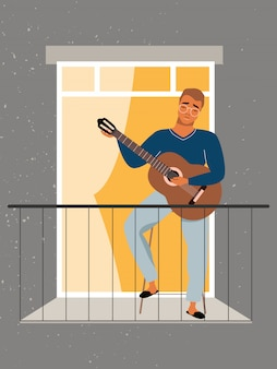 Young man plays guitar at the balcony. quarantine and self-isolation concept. staying at home during the pandemic. man in the window learning how to play guitar. guitar lessons at home.