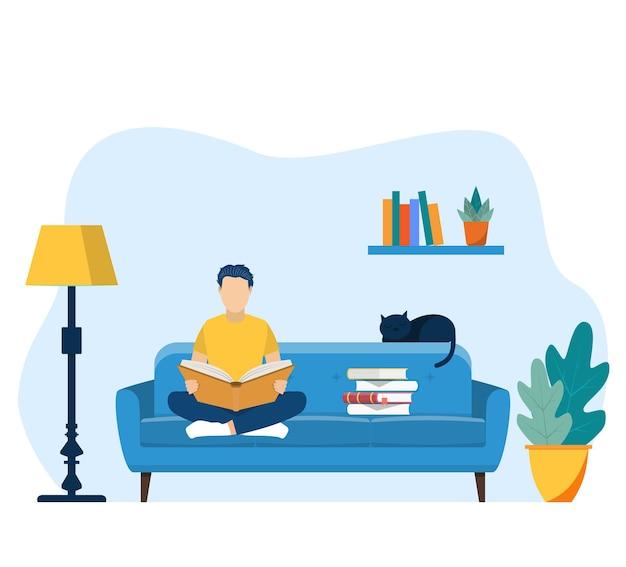 Молодой человек читает книгу на стуле у себя дома.