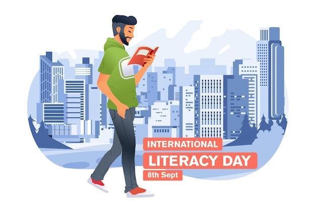 国際識字デーの背景として都市の建物と都市公園の屋外を歩きながら本を読んで若い男