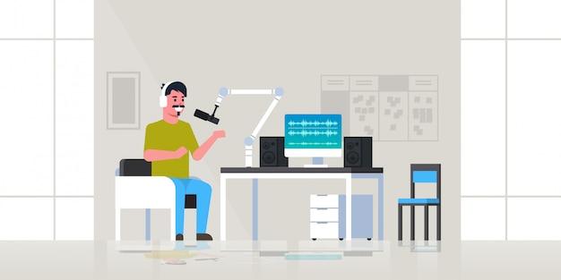 Молодой человек записывает подкаст в студии подкастинг вещание онлайн радио концепция парень в наушниках разговаривает с микрофоном полная длина горизонтальный