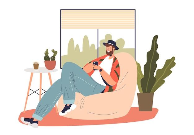 ソーシャルメディアに投稿し、メッセンジャーでテキストメッセージを手にスマートフォンを持って自宅でリラックスしている若い男