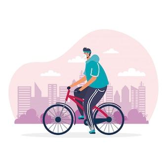 若い男が医療マスクを身に着けている自転車スポーツに乗って