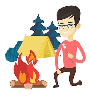 若い男がキャンプファイヤーでマシュマロを焙煎します。