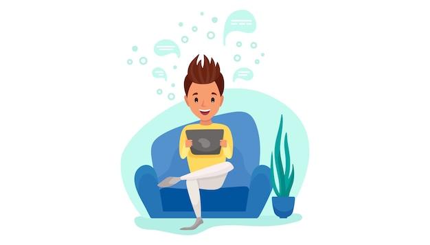 Молодой человек сидит с планшетом на диване у себя дома. дистанционное рабочее. фриланс, онлайн-обучение