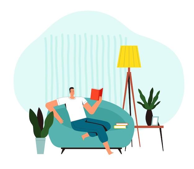 若い男は肘掛け椅子に座って本を読みます。