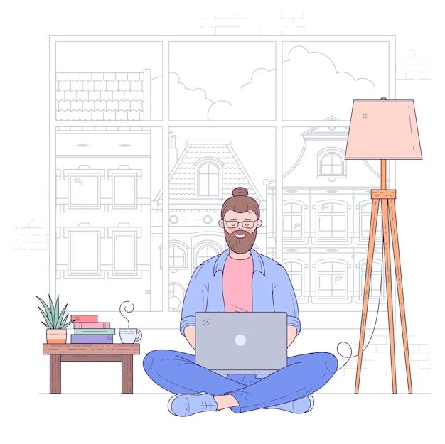 若い男は、ノートブックを持ってコーヒーテーブルの近くのあぐらをかいて床に座って、オンラインで働いています。