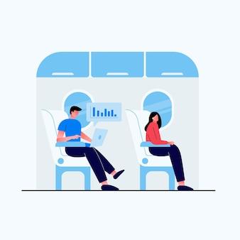 Giovane che si siede in aeroplano che lavora al computer portatile