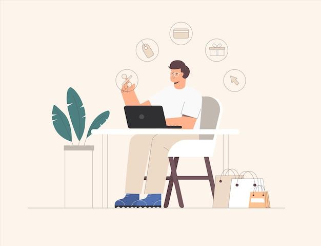 Молодой человек сидит за столом с ноутбуком и делает покупки в интернете