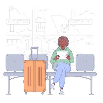空港ターミナルに座っている若い男。旅行と休暇の概念。