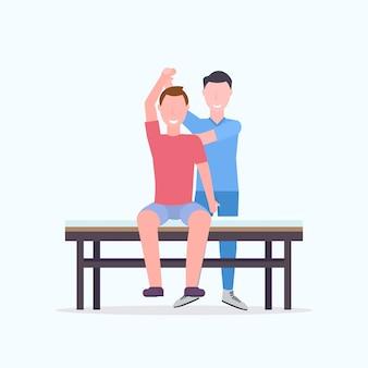 Молодой человек, сидящий на столе массажист терапевт делает лечение лечение массаж тела пациента мануальная терапия физиотерапия концепция