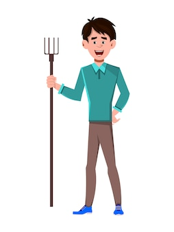 Young man standing with holding agricultural fork