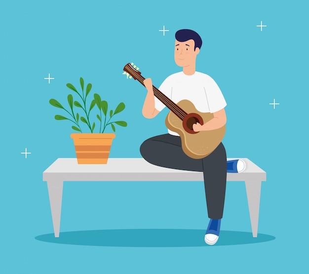 若い男は家でテーブルにギターを弾く