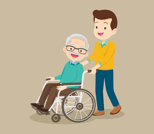 Молодой человек гуляет с пожилым мужчиной в инвалидной коляске
