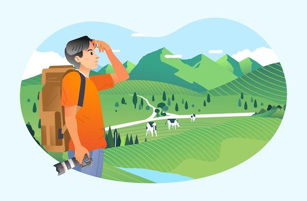 Молодой человек турист приносит камеру и наслаждается видом на красивый пейзаж в сельской местности