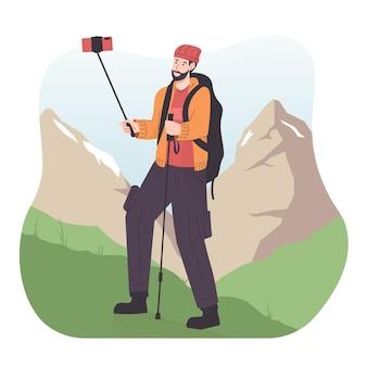 스마트폰을 사용하여 비디오를 녹화하는 동안 배낭을 메고 산에서 하이킹을 하는 젊은 남자 여행자