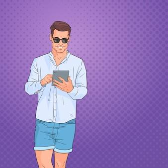 Молодой человек с помощью планшетного компьютера в сети над поп-арт красочный фон в стиле ретро
