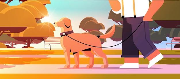 公園の男性の所有者とペットのコンセプトとかわいい家畜の友情で犬と一緒に歩く若い男