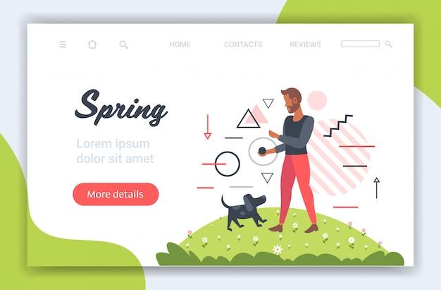 ペットの春の時間の概念でリラックスした公園の男で屋外犬と一緒に歩いている若い男