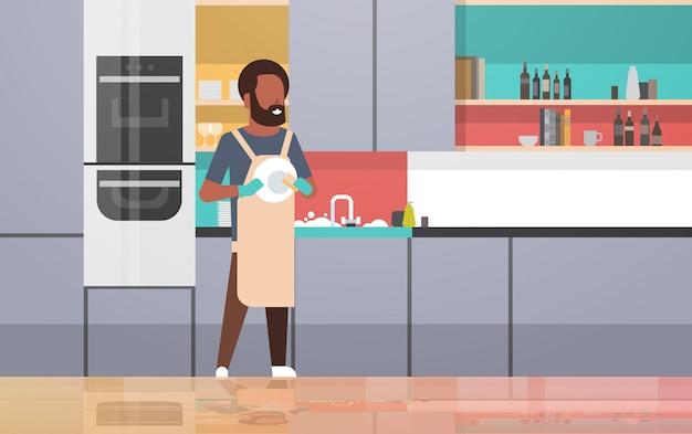 若い男が家事食器洗いコンセプトモダンなキッチンインテリア水平全長をやって皿を拭く男を皿洗い