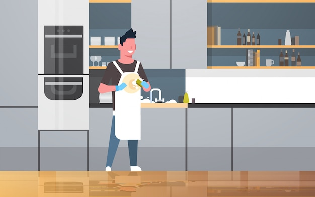 Young man washing dishes guy wiping plates doing housework dishwashing concept modern kitchen interior