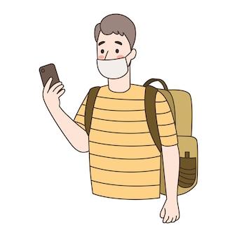 若い男はスマートフォンを使用してフェイスマスクを着用します