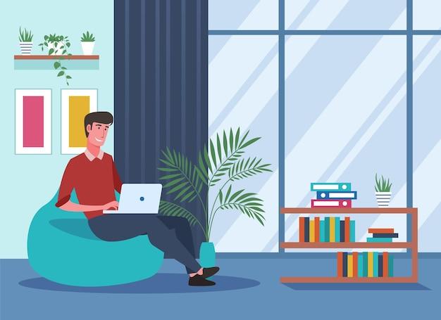 ノートパソコンで作業し、自宅でお手玉の椅子に座っている若い男