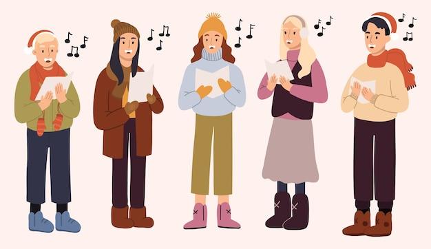 Молодые мужчины и девушки, одетые в верхнюю одежду, поют рождественские гимны.