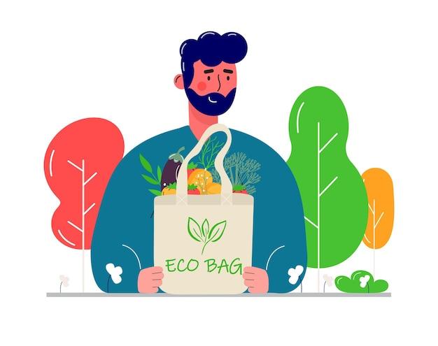 エコナチュラルバッグを購入して運ぶ若い男性。環境への配慮、ゼロウェイスト、菜食主義、。エコロジカルな食料品の買い物、野菜や果物が入った再利用可能なフレンドリーな買い物かご。