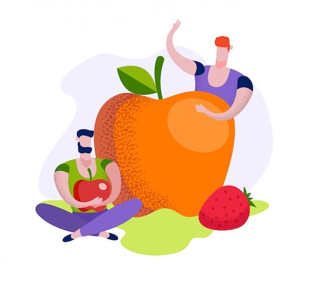 Молодые люди сидят за огромным спелым яблоком, клубникой