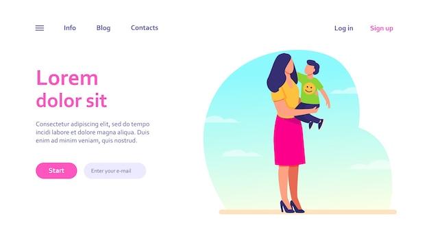幼児の子供を腕に抱いている若いお母さん。母と息子が屋外に立って、抱き締めます。母性、育児、ウェブサイトのデザインやウェブページのランディングのための家族の概念