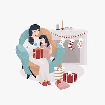 Young mother and daughter sit in a chair by the fireplace and open christmas presents