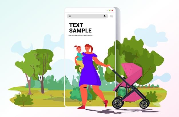 Молодая мать держит новорожденного ребенка и толкает коляску семья гуляет в парке концепция материнства экран смартфона пейзажный фон