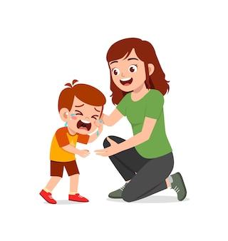 Молодая мать обнимает плачущего маленького мальчика и пытается утешить