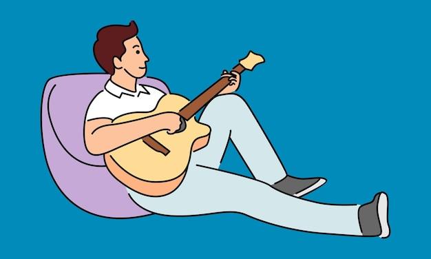 Молодой музыкант играет на гитаре