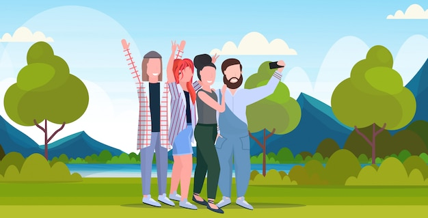 Young people group taking selfie photo on smartphone camera casual friends men women having fun posing outdoor nature landscape mountains background full length horizontal