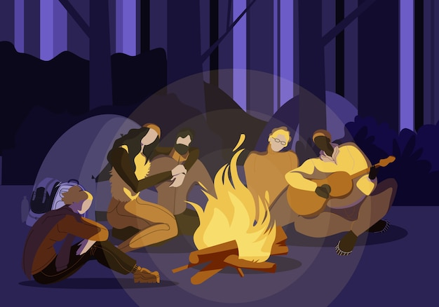 Young people sitting around campfire at night time
