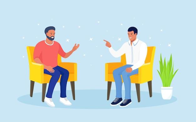 Молодые люди сидят в кресле и разговаривают. говорят мужчины, общаются коллеги. обсуждение друзей. командная работа. социальные сети, диалог и беседа. люди спрашивают, отвечают на вопросы
