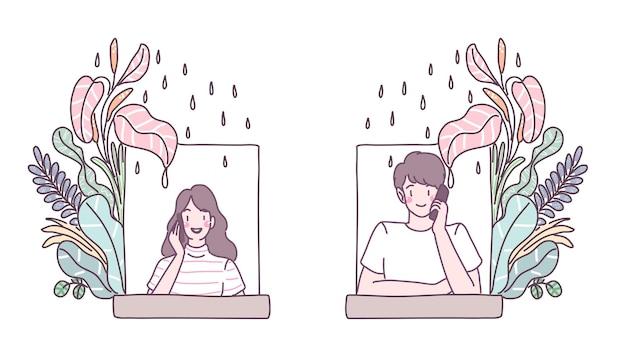 I giovani si sono parlati al telefono nella finestra con fiori e pioggia.