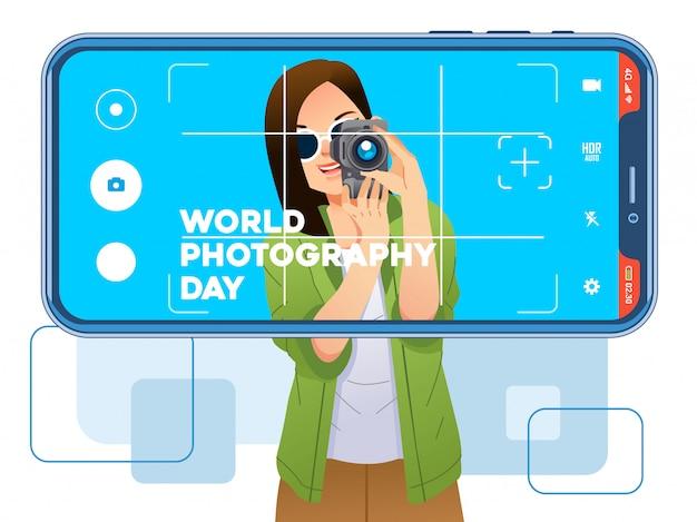 Молодая красивая девушка позирует с камерой и сфотографирована с помощью смартфона. используется для плаката, изображения веб-сайта. всемирный день фотографии