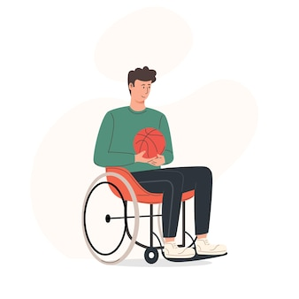 Young smiling man sitting in wheelchair while holding a basketball