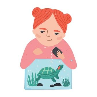 Молодая улыбающаяся рыжая женщина или девочка кормит свою черепаху