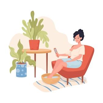 Молодая улыбающаяся женщина, сидящая в кресле, делает педикюр