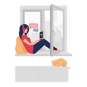 창턱에 집에서 일하는 젊은 웃는 여자.